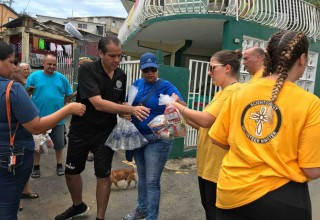 Volunteer Ministers help Jorge Navarro Suárez (in black) distribute supplies to his constituents.