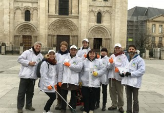 Volunteers from The Way to Happiness Foundation of France gather to launch a neighborhood cleanup.